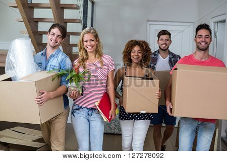 Portrait of friends smiling while carrying carton in new house