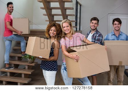 Portrait of cheerful young friends carrying carton in new house