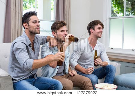 Happy young male friends drinking beer while watching TV at home