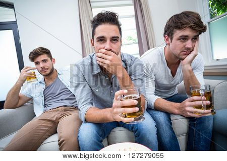 Upset young male friends drinking alcohol while watching TV at home
