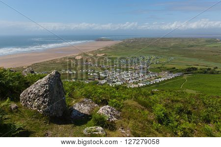 View from the top of Rhossili Down to Burry Holms and Hillend The Gower peninsula Wales UK in summer with caravans and camping on the campsite