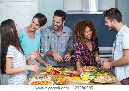 Happy multi-ethnic friends preparing pizza on kitchen table at home