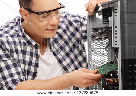 Young PC technician assembling a desktop computer isolated on white background