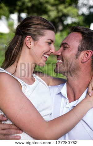 Smiling happy young couple romancing in lawn