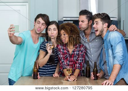 Multi-ethnic young friends making faces while taking selfie by table in kitchen