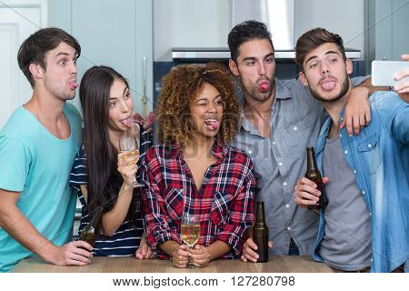 Multi-ethnic friends making faces while taking selfie by table in kitchen