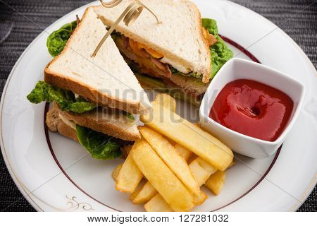 Sandwich with fried eggs, bacon and lettuce served with french fries and ketchup