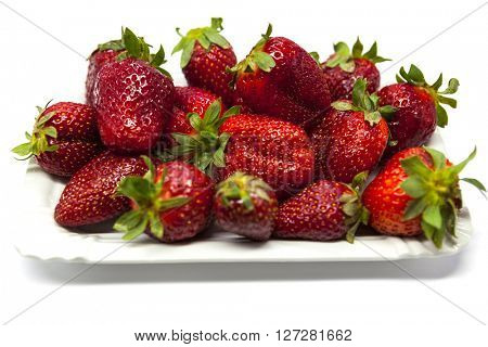 Fresh strawberries on a plate on white background.