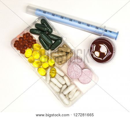 Different pills, medications, the pills in the box for drugs closeup with medicine with a syringe on white background