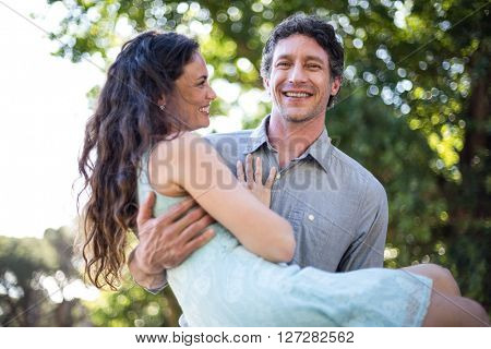 Portrait of smiling happy husband carrying wife at park