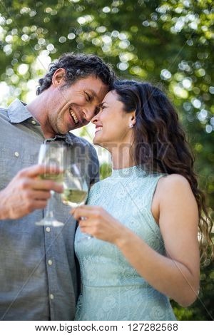 Joyful couple holding wineglasses in lawn