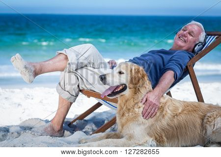 Mature man resting on a deck chair listening to music petting his dog on the beach