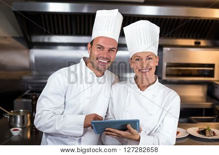 Portrait of smiling happy chefs holding clipboard in commercial kitchen