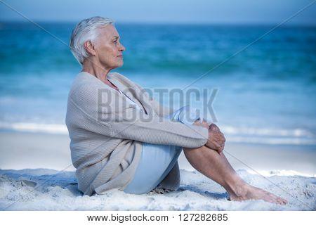 Thoughtful mature woman meditating on the beach