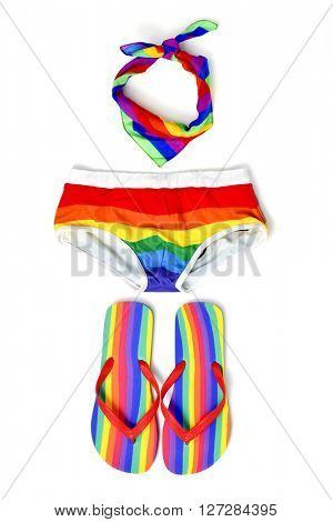 high-angle shot of different rainbow-patterned summer stuff, such as a pair of flip-flops, a kerchief and a male swimsuit, on a white background