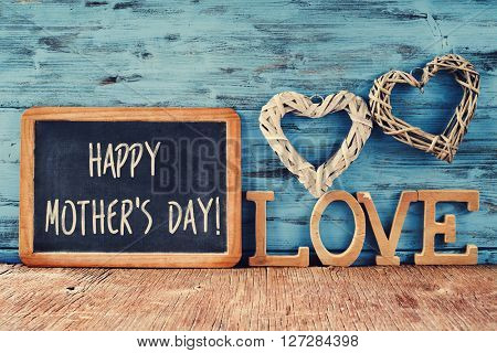 the text happy mothers day written in a chalkboard placed next to some wooden letters forming the word love and some rustic handmade hearts, against a rustic blue background