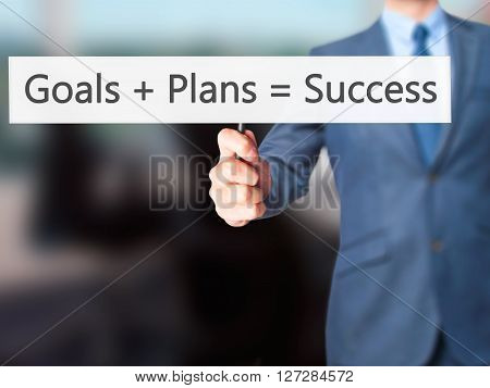 Goals  Plans  Success - Businessman Hand Holding Sign