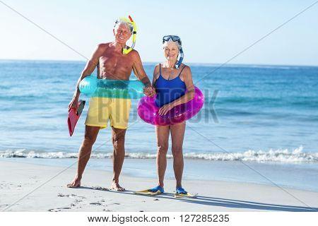 Senior couple with beach equipment at the beach