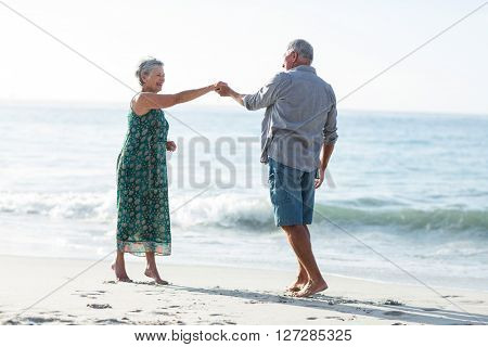 Senior couple dancing at the beach on a sunny day