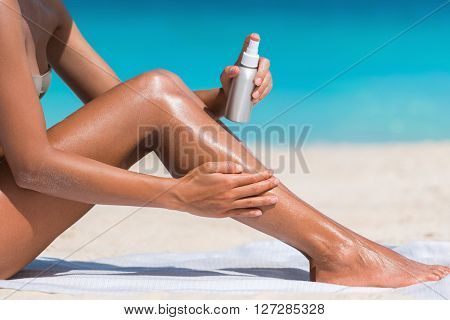 Sunscreen suntan lotion in spray bottle. Young woman in spraying tanning oil on her leg from bottle. Lady is massaging sunscreen lotion while sunbathing at beach. Female model during summer vacation.