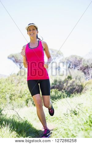 Fit smiling woman jogging in the countryside
