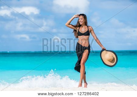 Woman in black bikini and sarong walking on beach. Elegant sexy girl wearing fashion beachwear putting on sunglasses and straw hat for sun uv protection enjoying her summer vacation in the Caribbean.