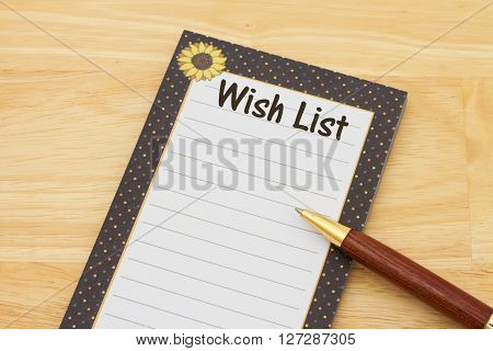 Blank wish list of notepad and paper A notepad and pen on a desk with text Wish List and copy-space