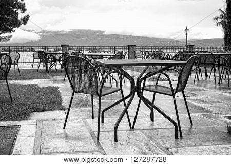 Tables and chairs on a public dehor, over the Garda lake shores (Lombardy, Northern Italy), early springtime. Black and white photo
