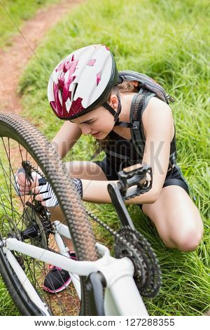 Woman fixing her bike in the countryside