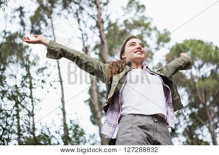 Smiling woman with arms up in the countryside