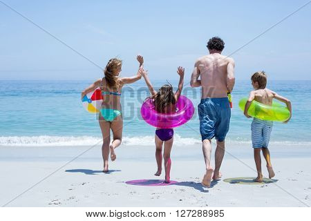 Rear view of cheerful family running towards sea with swimming equipment