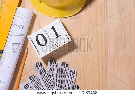 May 1st. Image of may 1 white blocks wooden calendar with construction tools on the table. International Workers' Day. Labor day concept.