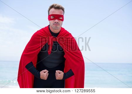 Portrait of serious man in superhero costume standing at sea shore