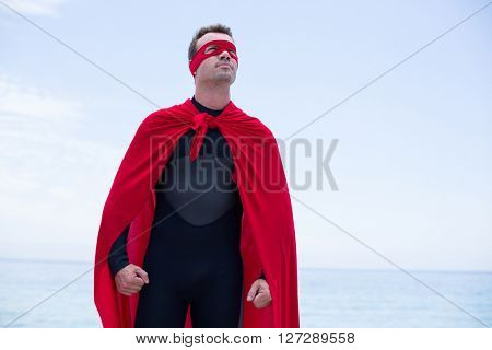 Low angle view of confident man wearing superhero costume standing by sea