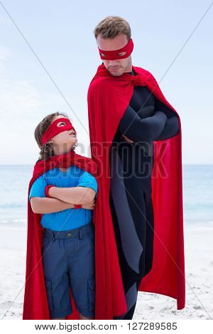 Father and son in superhero costume standing with arms crossed at beach