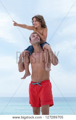 Father looking at son showing while carrying him on beach