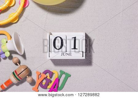 June 1st. Image of june 1 white blocks calendar with toy tools on sandy background. First summer day. Empty space for text. Happy Childrens Day. Copy space view from above