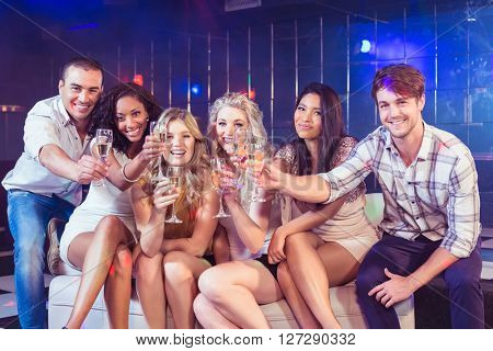 Friends toasting with champagne in a club