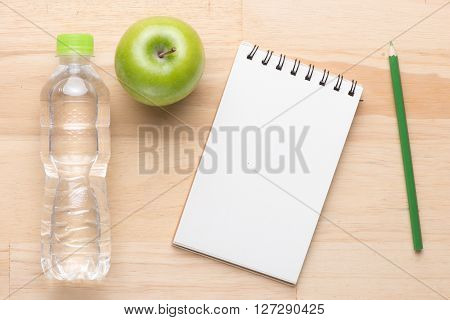 Fitness training programme with dumbbells, mix fruits, towel, blank notebook. View from above with copy space. Weight loss concept