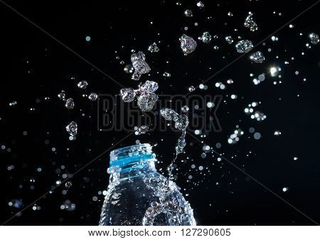 Water Splashes From The Bottle On Black Background