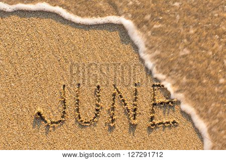 June - word drawn on the sand beach with the soft wave. Months series of 12 pictures.