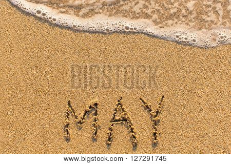 May - word drawn on the sand beach with the soft wave. Months series of 12 pictures.