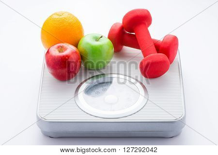 Tape measure on bathroom scale for weight of human body, dumbbells for fitness and fresh fruits. Concept of healthy lifestyle and slimming