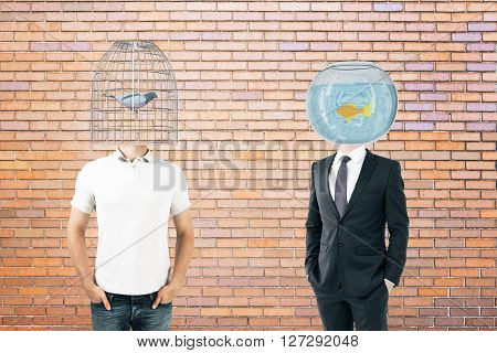 Businessperson and casually dressed man with fishtank and birdcage instead of heads on brick background