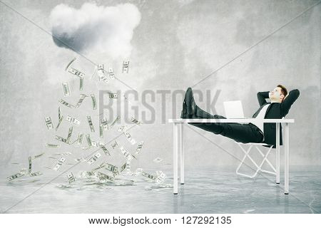 Financial growth concept with businessman sitting at table with feet up and looking at abstract money rain in concrete room. 3D Rendering