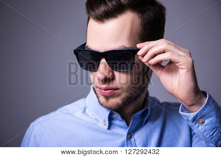 Close Up Portrait Of Young Handsome Man In Sunglasses Over Gray