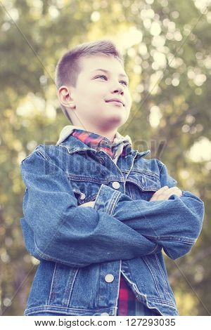 Confident young boy standing in a field, park, resting enjoying a happy air in jeans jacket shirt ** Note: Soft Focus at 100%, best at smaller sizes