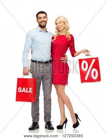 people, sale, discount and holidays concept - happy couple hugging with red shopping bags