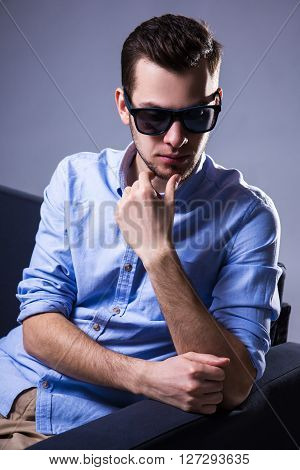 Portrait Of Handsome Man In Sunglasses Sitting On Sofa And Thinking About Something