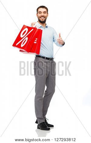 people, sale, discount and holidays concept - smiling man holding red shopping bags with percentage sign and showing thumbs up gesture